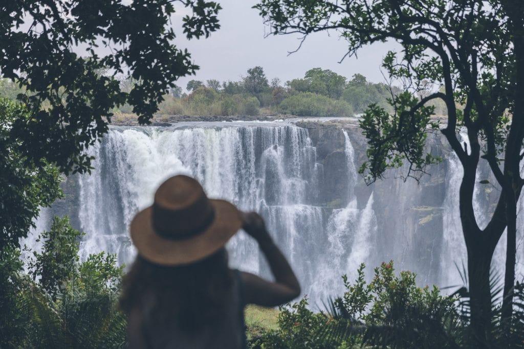A Matetsi Victoria Falls guest looking at Victoria Falls through binoculars